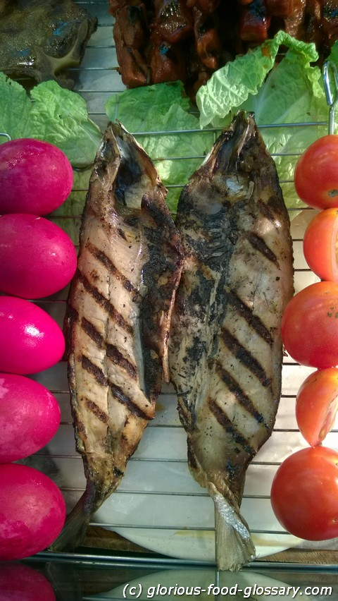 Inihaw na Bangus or Grilled Milkfish is best eaten with salad made from slices of fresh tomatoes and slices of  Itlog na Maalat (red salted eggs)